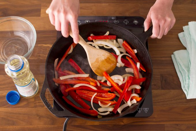 Sliced veggies in a cast-iron skillet being stirred by a wooden spoon