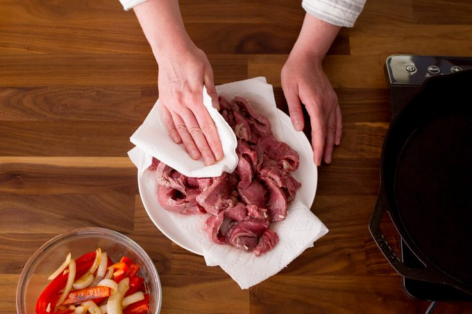 Sliced meat on a bed of paper towel being patted down