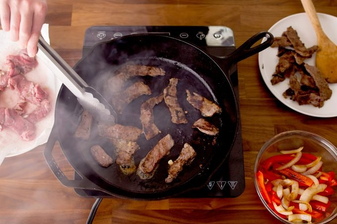 Person stirring sliced meat in a cast-iron skillet with metal thongs