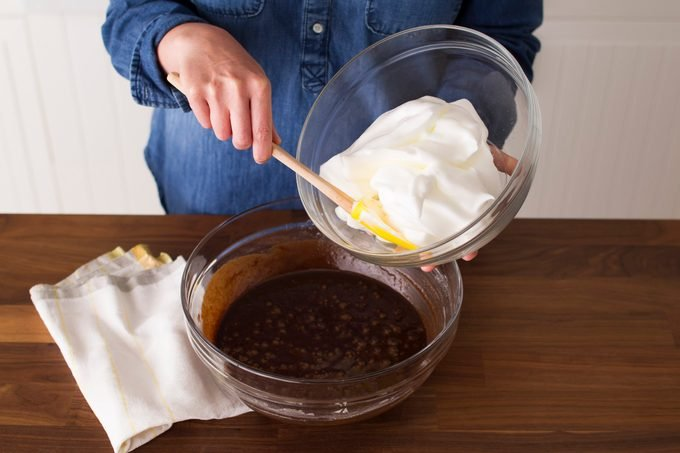 Person digging into a bowl of whipped cream with a spatula while standing over a bowl of melted chocolate
