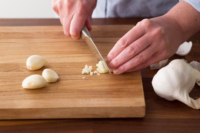 Person carefully slicing into a clove of garlic