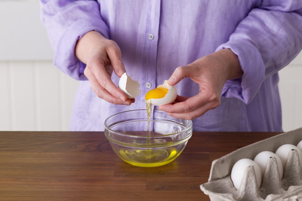Person carefully using the egg's own shell to separate the yolk from the whites