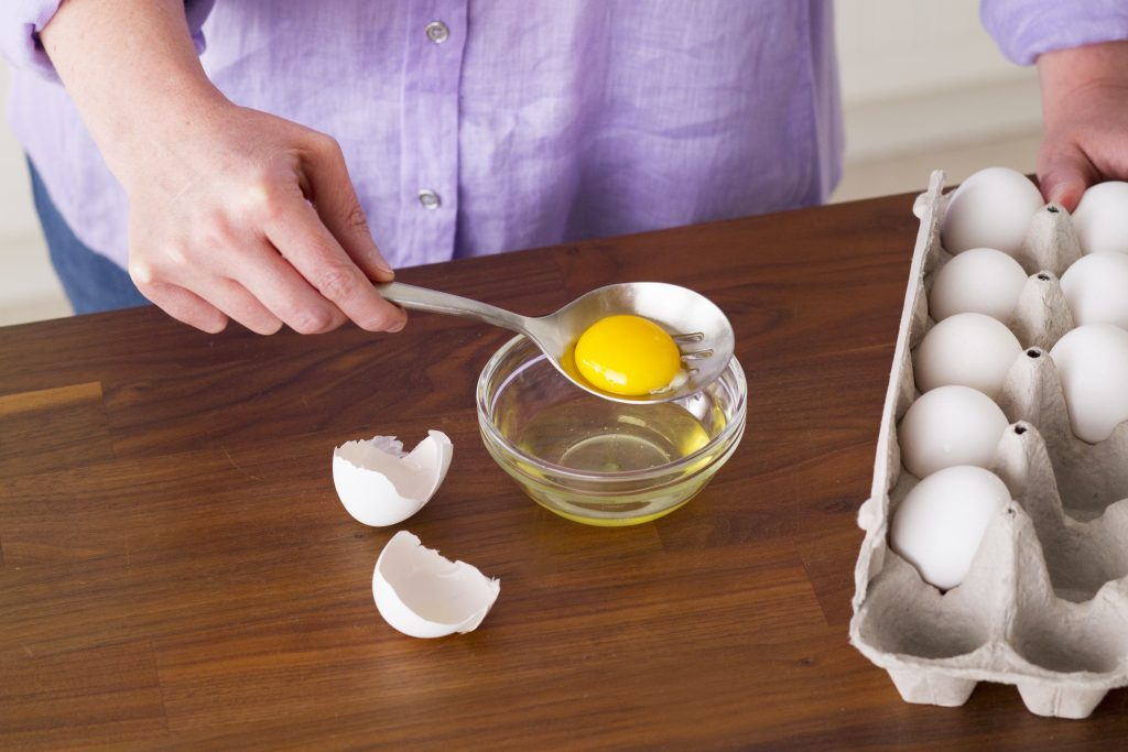 Person holding the insides of an egg inside a slotted spoon to separate out the whites