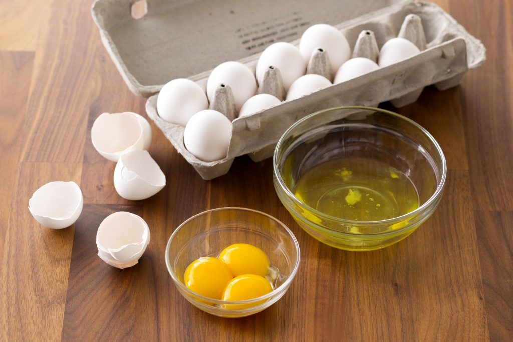 How to separate egg whites from yolks taste of home carton of eggs besides two bowls one with egg whites and the other with yolks forumfinder Gallery