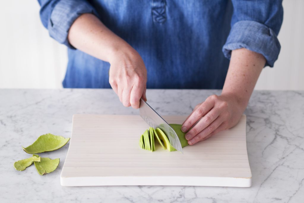Person using a knife to slice a peeled avocado half