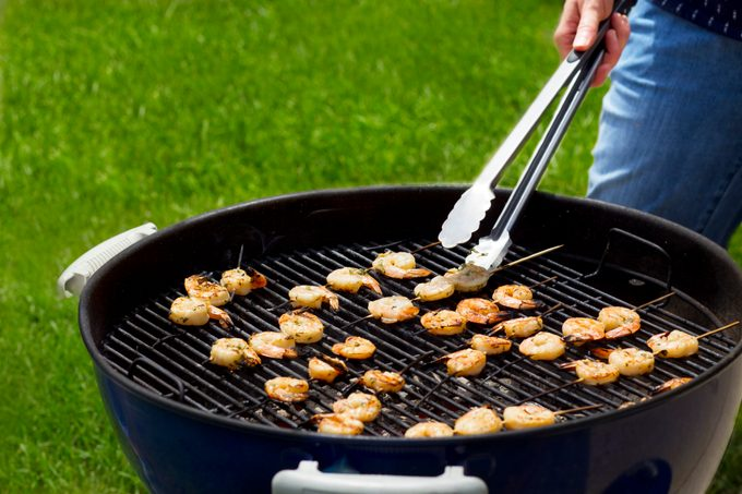 Person using metal tongs to flip skewered shrimp on a charcoal grill