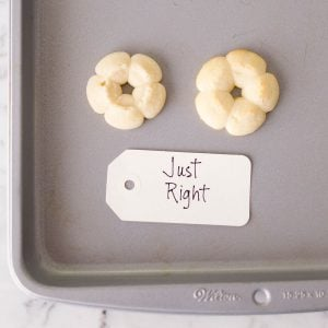Perfect-sized raw spritz cookies on a baking sheet