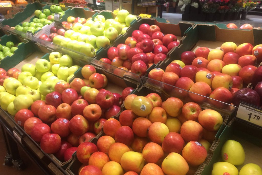 Rows of different types of apples on grocery store shelves