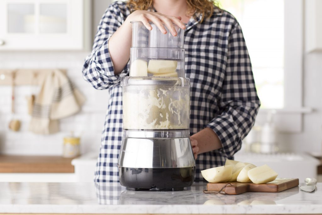 Person using a food processor to shred potatoes the easy way