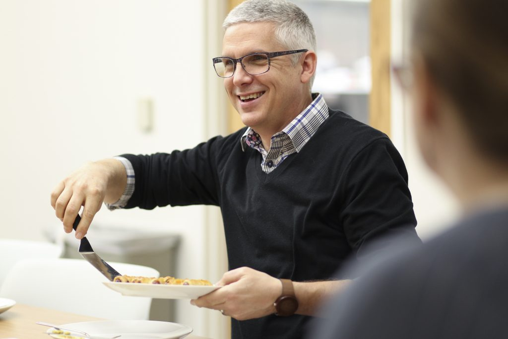Smiling man handing out food with a spatula from a plate he's holding