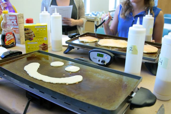 Griddle with pancake batter shaped into a smiling face
