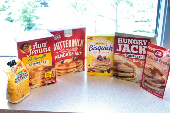 Six different brands of pancake mixes lined up in front of a window
