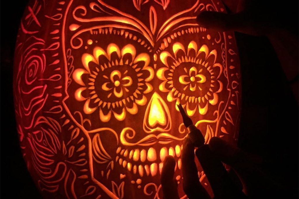 Intricately carved Day of the Dead skull on a pumpkin