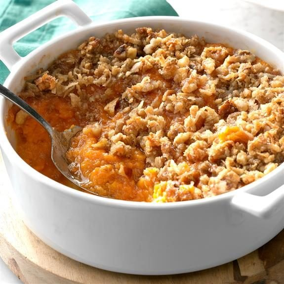 Sweet potato casserole in a pot with a section of it disturbed by a large spoon