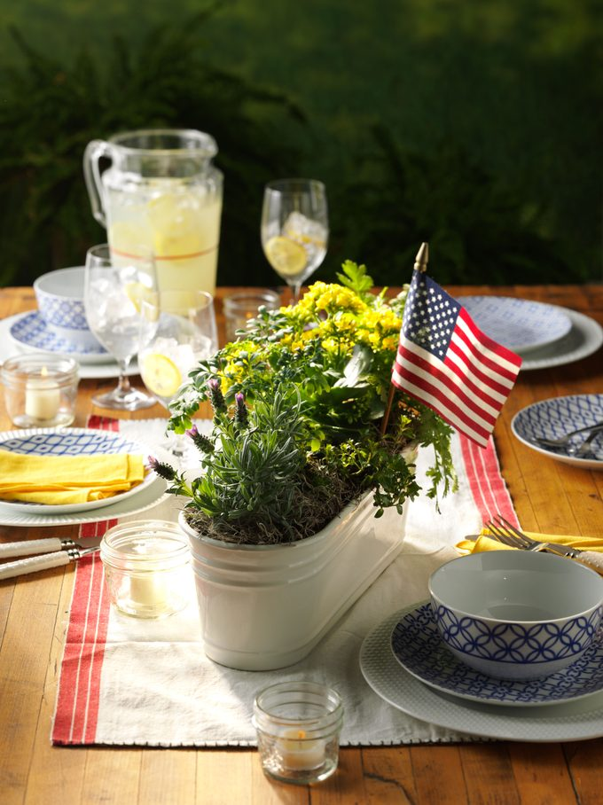 Set patio table featuring a pitcher of lemonade and a potted centerpiece with an American flag