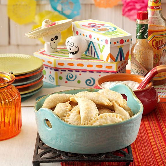 Table decorated with tiny painted skulls wearing hats and brightly colored plates. A blue pot of pinched pocket treats