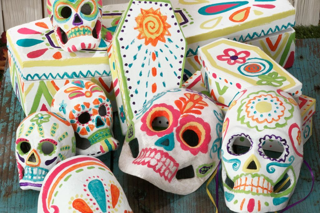 Wooden table filled with brightly decorated skulls and coffins of different sizes