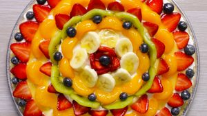 Summer dessert pizza with rows of different sliced fruit