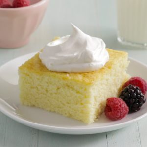 Square of hot milk cake topped with whipped cream on a plate with several berries lined up along one side