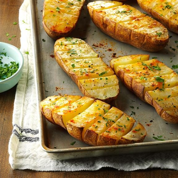 Well-seasoned baked potatoes scored deep and resting on a baking sheet