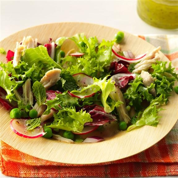 Spring chicken and pea salad filling a plate over a plaid tablecloth