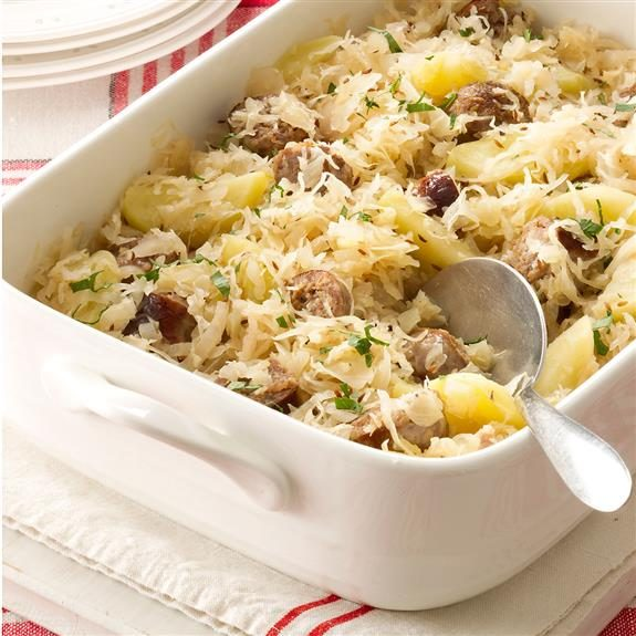 Sauerkraut casserole in a white 13x9 dish and accompanied by a large spoon