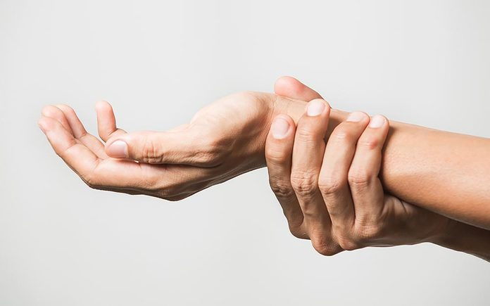 Person holding onto one wrist with their other hand