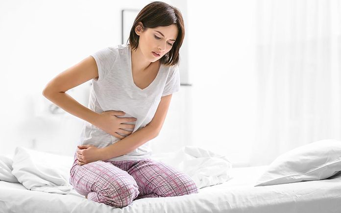 Woman in pjs clutching her stomach as she rising out of bed