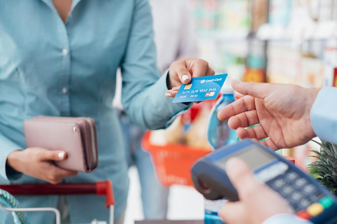 Person handing over a credit card to a cashier at a store