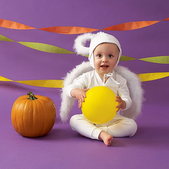 Baby in a white outfit complete with a fuzzy halo and wings against a purple background with streamers