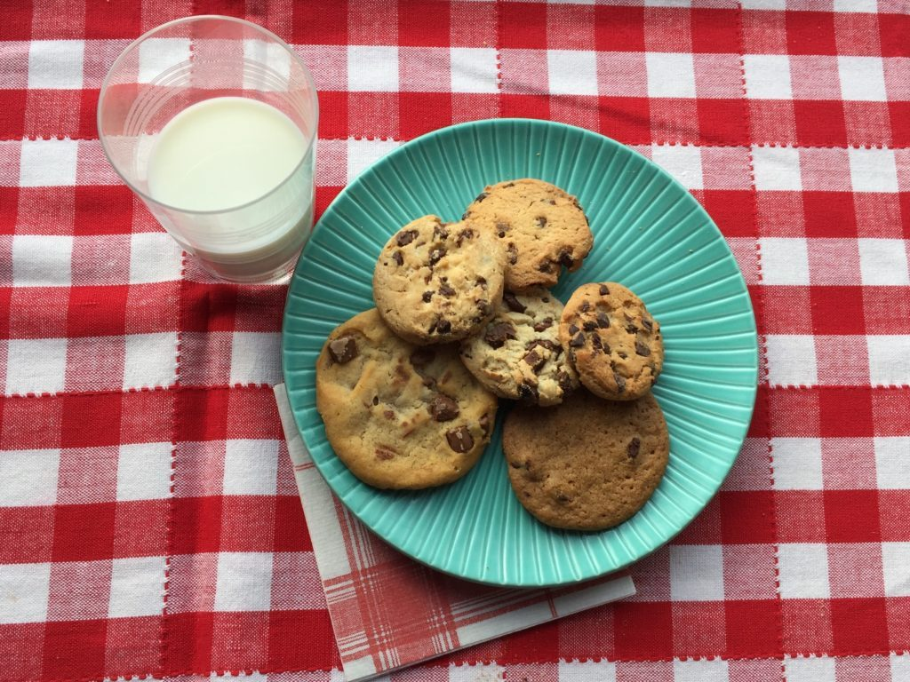 Blue plate filled with different brands of chocolate chip cookies with a glass of milk on the side