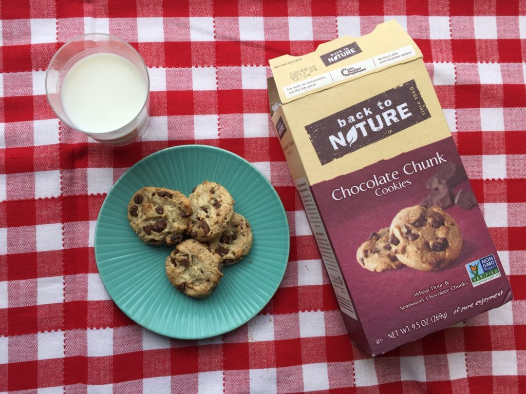 Package of Back to Nature chocolate chunk cookies beside a glass of milk and plate of cookies