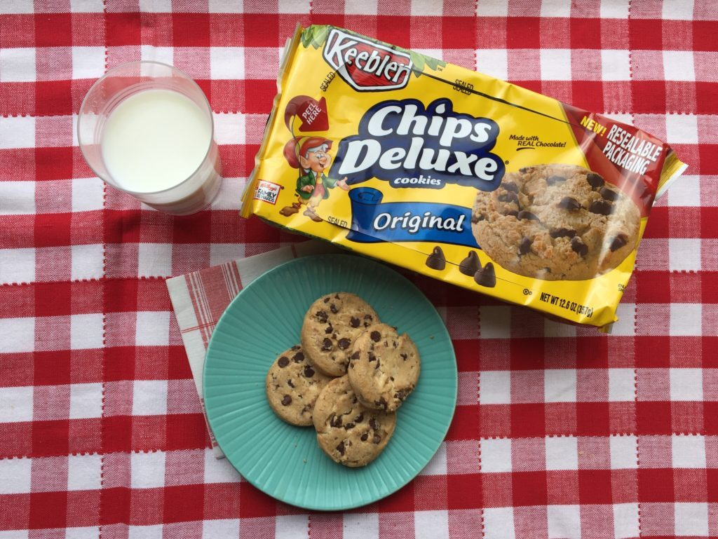 Package of Keebler deluxe chocolate chip cookies beside several cookies on a blue plate