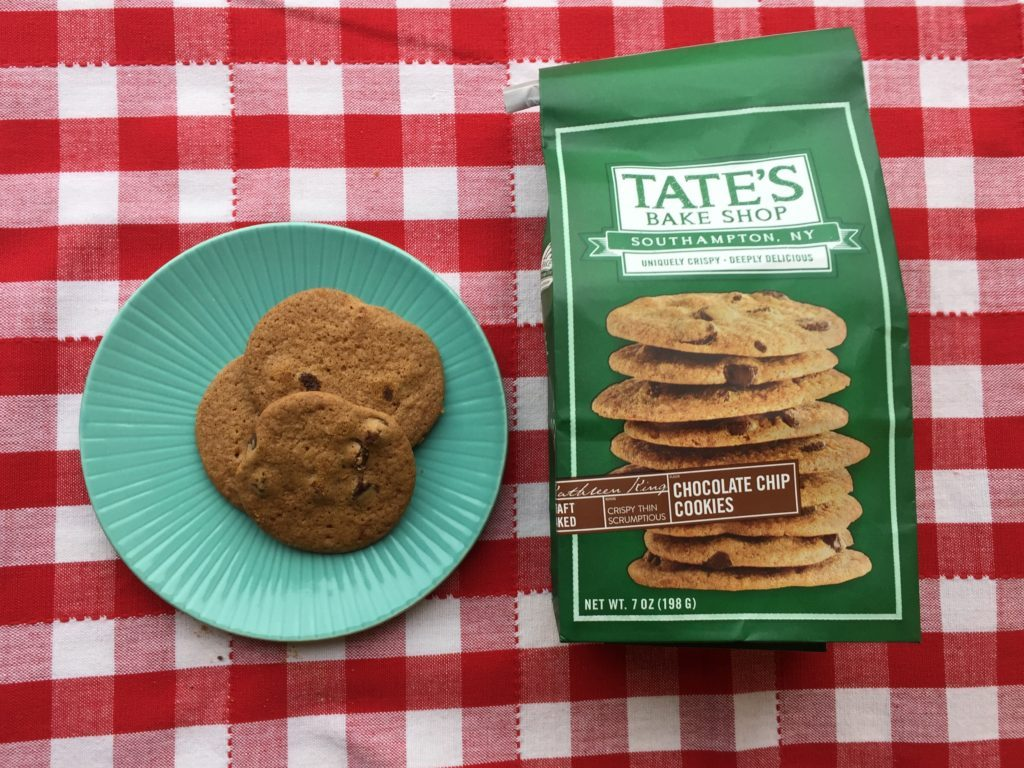 Package of Tate's Bake Shop chocolate chip cookies with two cookies out beside it on a blue plate