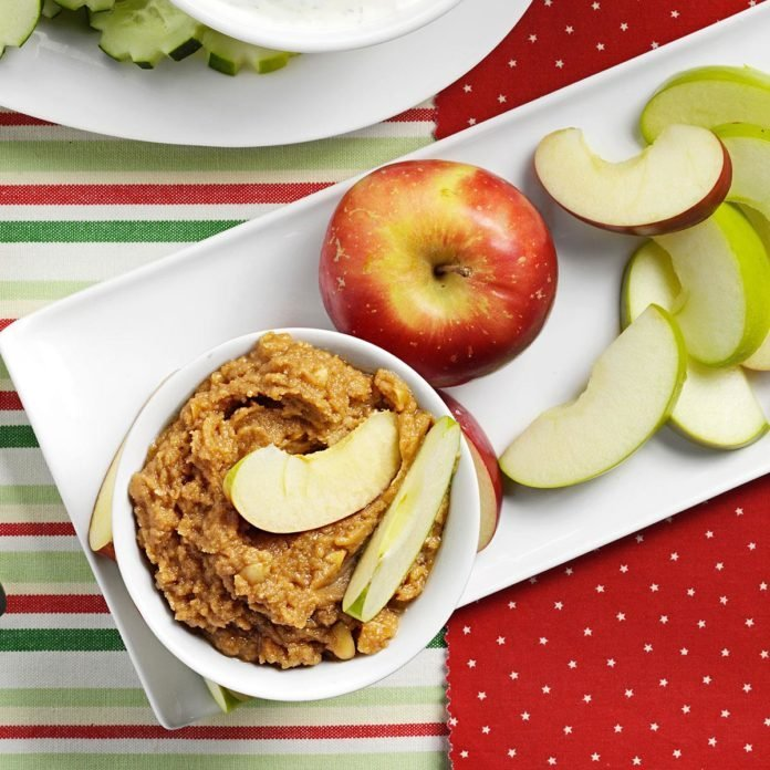 A plate with an apple appetizer of sliced apples and crunchy peanut butter apple dip