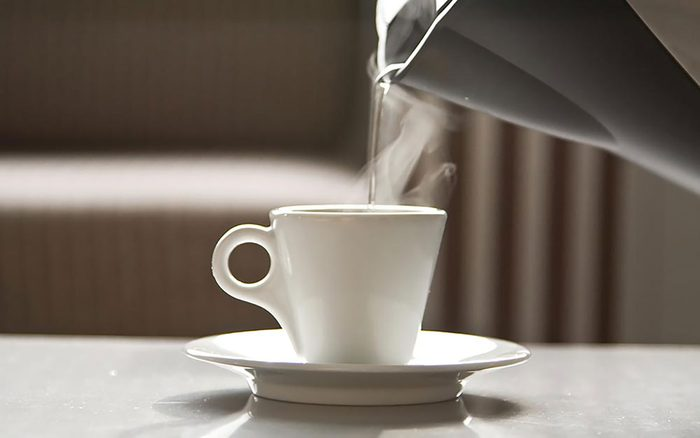 Hot water being poured in a small white cup