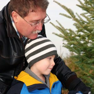 Father and son cutting down a Christmas tree