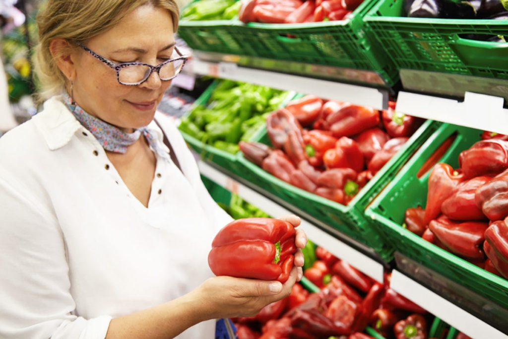 Good-looking senior woman wearing glasses holding red pepper, examining it with care, smiling while grocery shopping in supermarket, standing in front of boxes filled with fresh fruits and vegetables