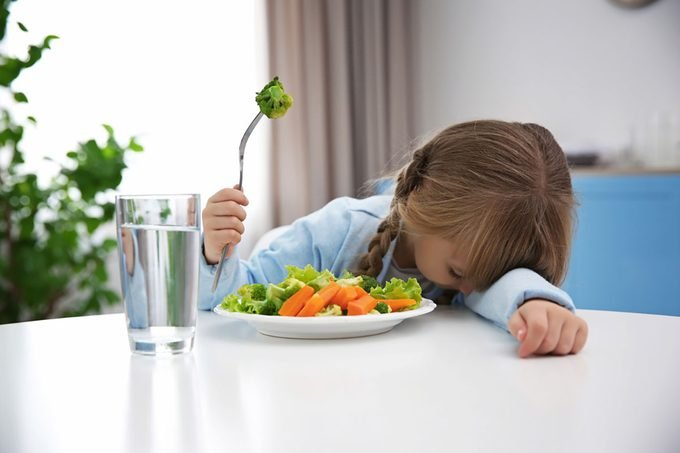 Small girl refusing to eat vegetable salad