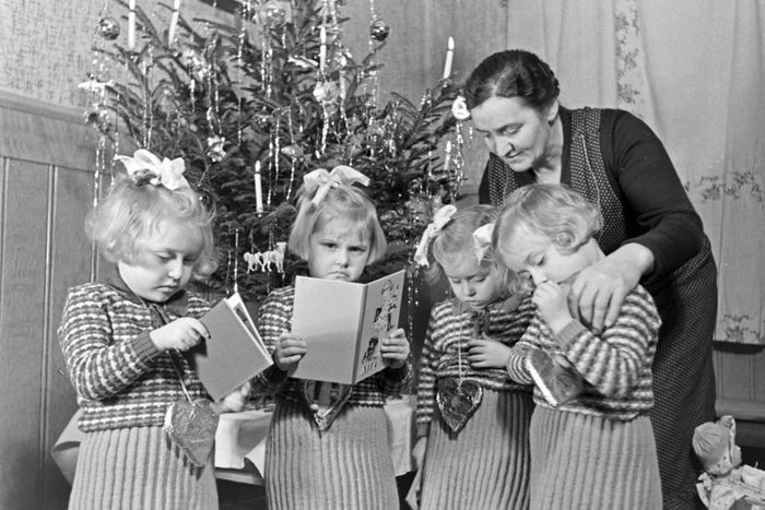 Four girls and woman standing by Christmas tree