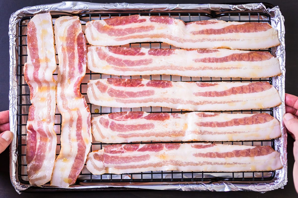 Raw bacon strips with fresh spices on a baking sheet.