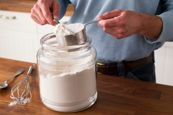 Person using a knife to even off the top of a measuring cup filled with flour