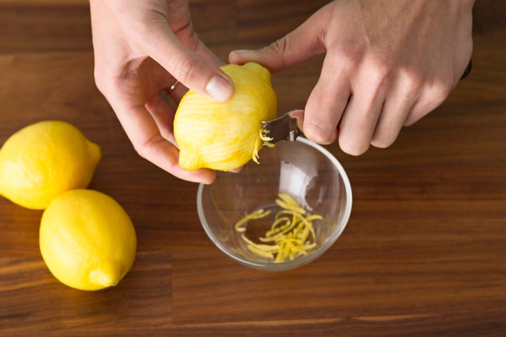 Person using a tool to scrape the zest from several lemons