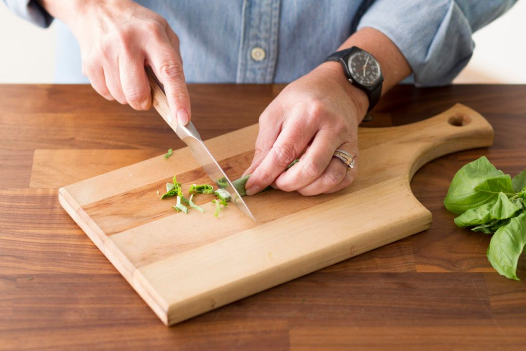 Person slicing their rolled basil into thin strips