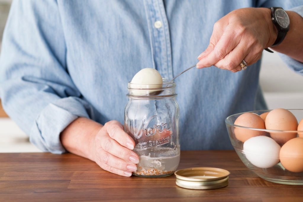 Using a spoon to remove a peeled egg from a mason jar with an inch of water