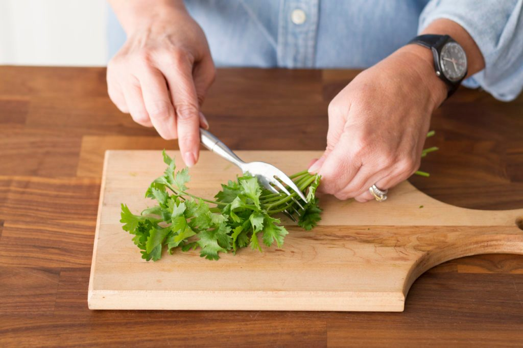 Using a fork to remove the leaves from a bundle of herbs by running the utensil up the stems