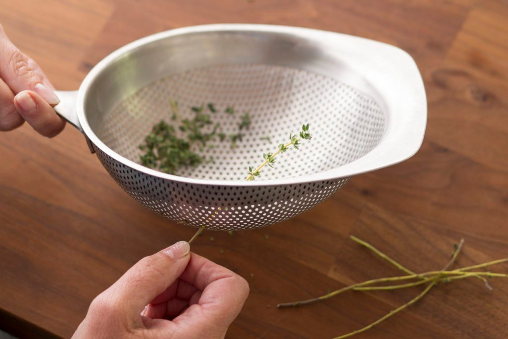 Person pulling a herb through the holes of a strainer to remove its leaves