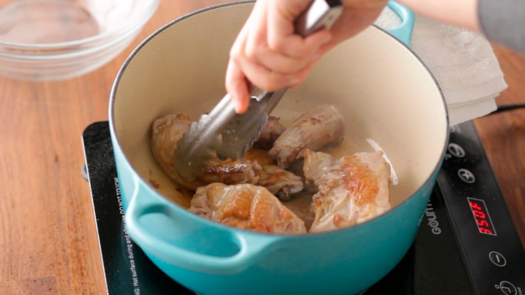 Chicken being flipped in a stockpot