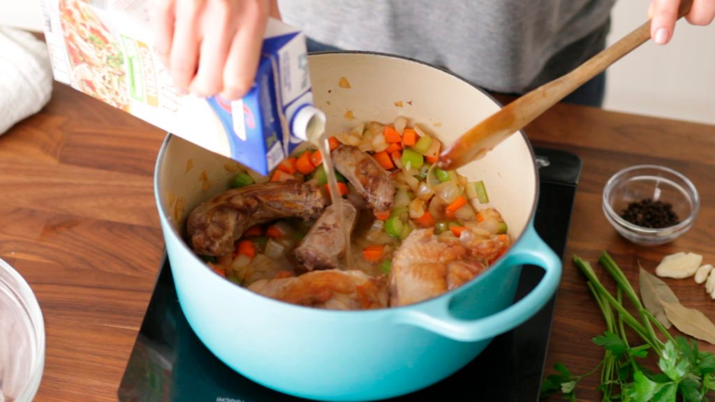 Chicken broth being added to the turkey bone and diced vegetables