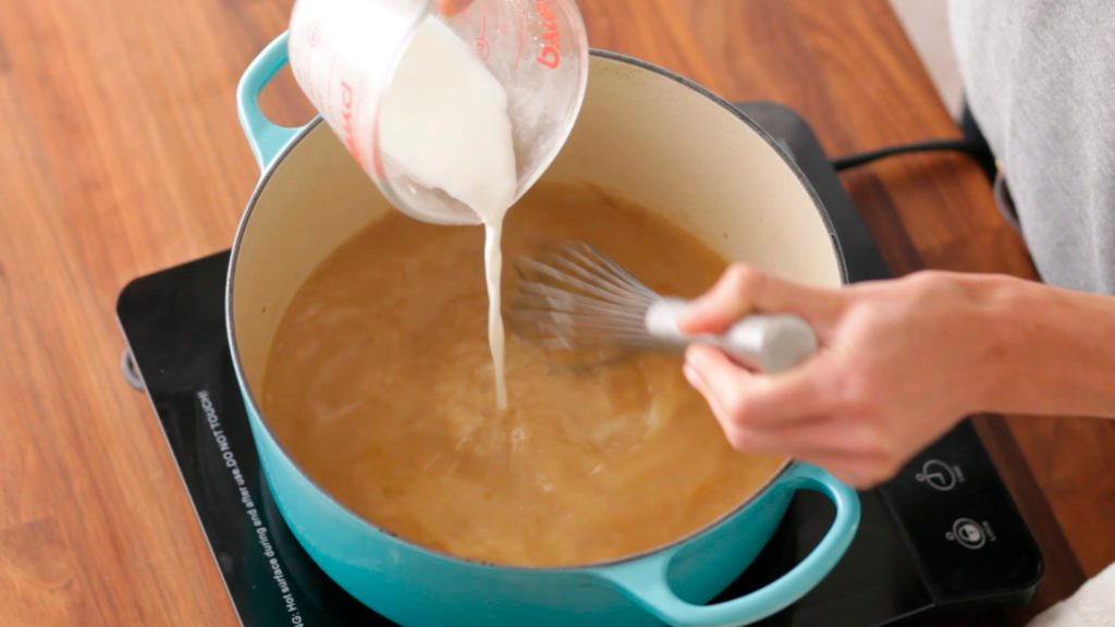 Cornstarch and cold water mixture being poured into the thickening gravy